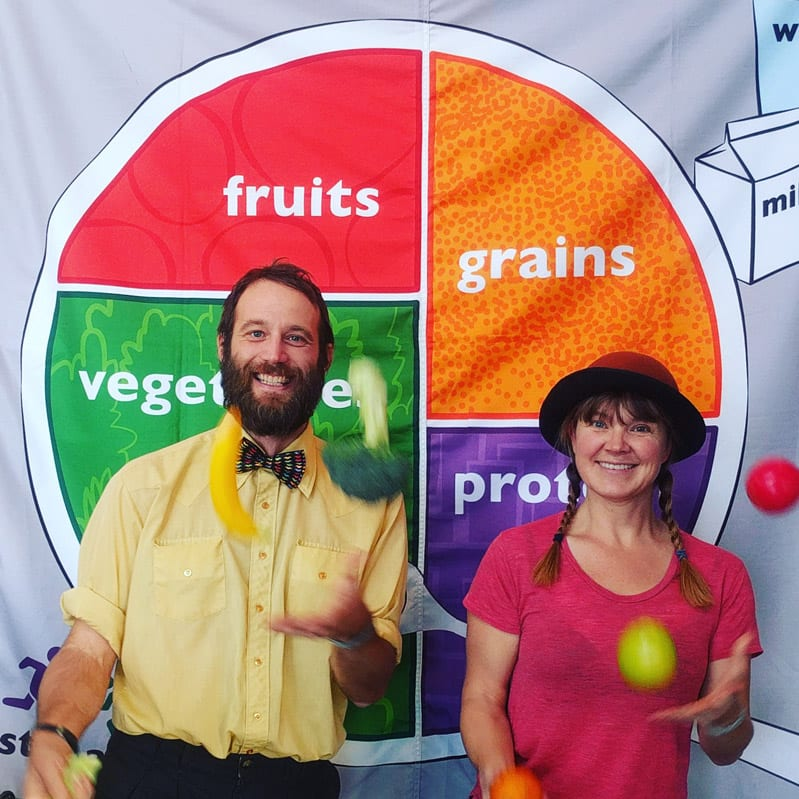 juggling produce in front of nutrition wheel
