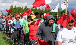 farm workers marching with red flags protest