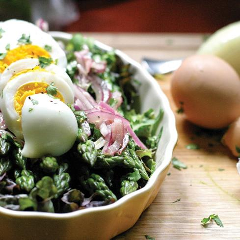 asparagus salad with hard-boiled eggs and onions in bowl next to egg shells