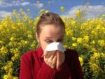 photo of woman sneezing into tissue near a field of blooming flowers