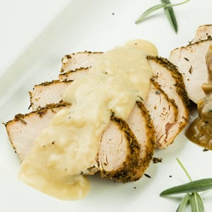 slices of roasted turkey fanned out on a white platter with gravy over the turkey and herbs on the side for holidays made easy
