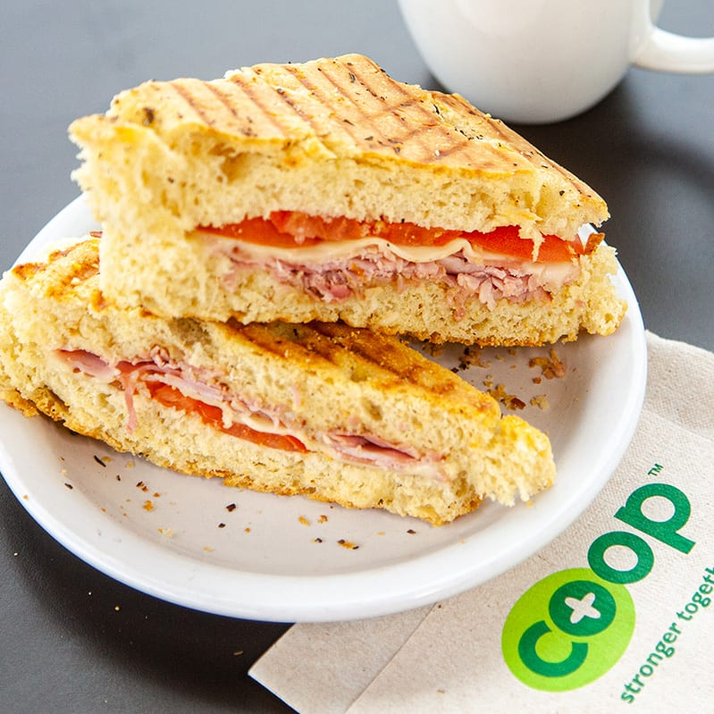 freshly grilled panini sandwich with grill marks split in half on a white plate with a co-op napkin and coffee cup alongside