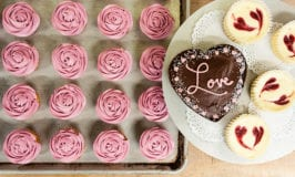 an array of valentine's day themed baked goods from the co-op bakery including a heart-shaped cake that says love, mini cheesecakes decorated with raspberry hearts, and cupcakes iced with pink frosting that looks like a flower bloom