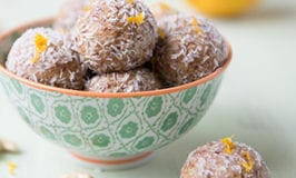 bowl filled with cashew orange date balls that are rolled in shredded coconut