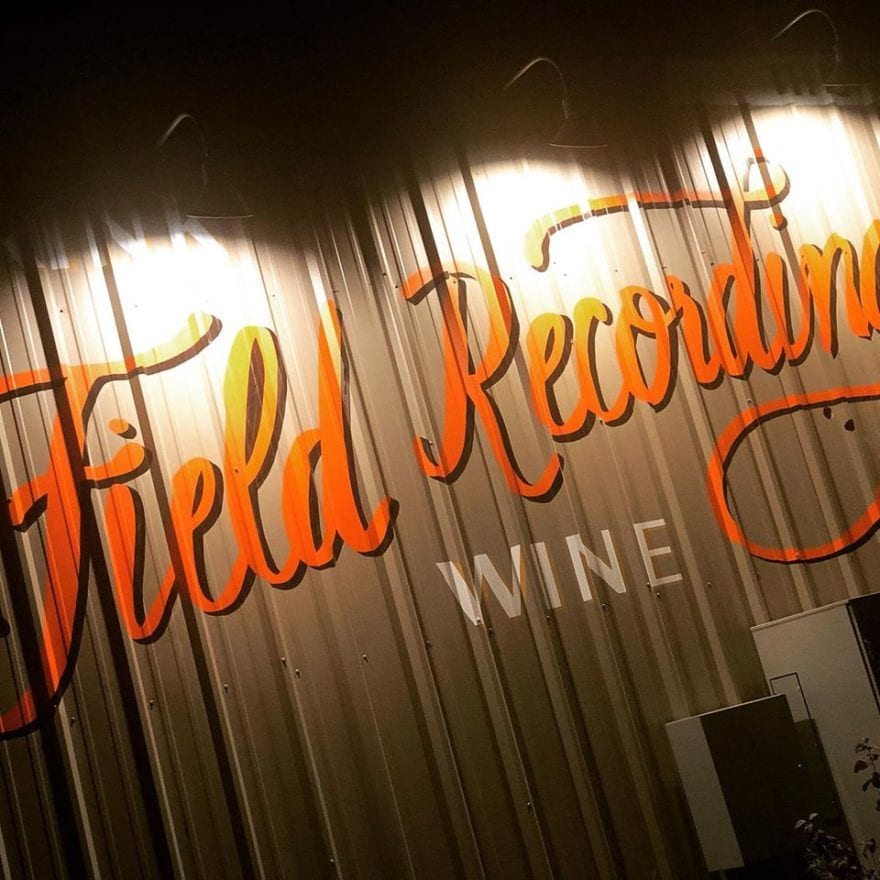 an exterior shot of the field recordings winery with the name projected on corrugated metal in orange script